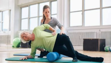 Female instructor helping senior woman using a foam roller for a myofascial release massage at gym